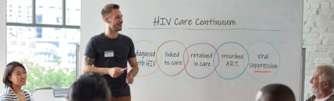 man in front of a white board, leading a discussion group regarding HIV